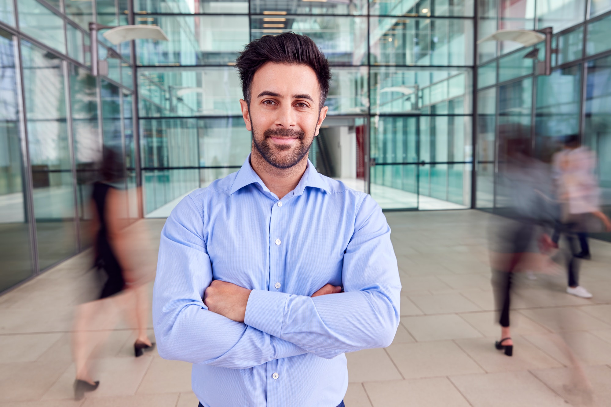 Portrait Of Businessman With Crossed Arms Standing In Lobby Of Busy Modern Office