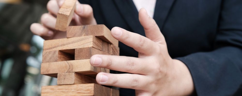businesswoman hand placing wood block on tower. growth, risk & strategy in business.