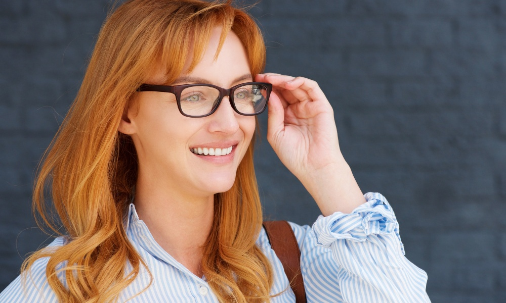 happy business casual woman with hand to glasses