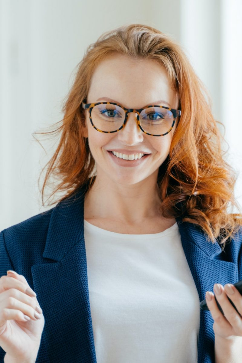 Happy female leader with ginger hair, wears spectacles, updates app on modern cell phone