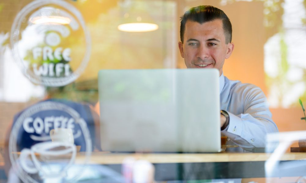 Happy young businessman using laptop at the coffee shop