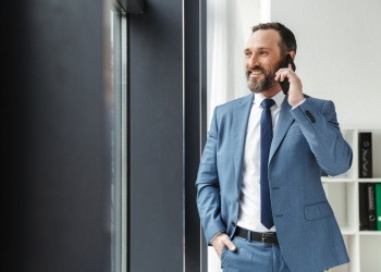 Photo of bearded smiling businessman in formal suit talking on cellphone