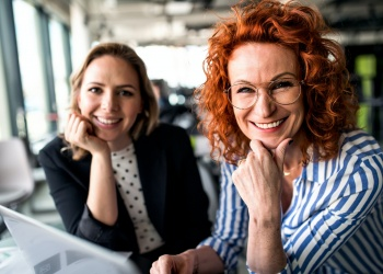 Two female business people sitting in an office, talking